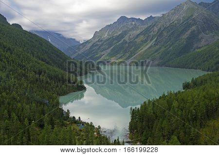 Reflection of mountains in the lake. Kucherla lake. Altai Mountains Russia. Overcast summer morning.