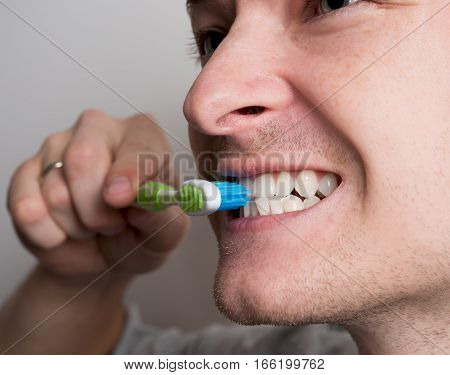 one men closeup cleans morning teeth brushing