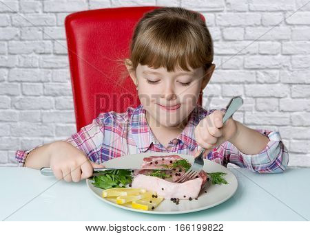 cute girl eats a piece of meat