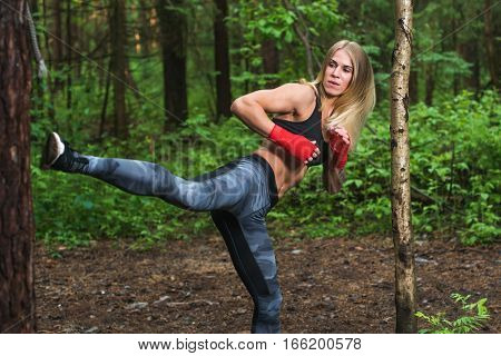 Fit woman doing kickboxing training, exercising, working out outdoors.