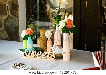 The wedding buffet table with vases and flowers