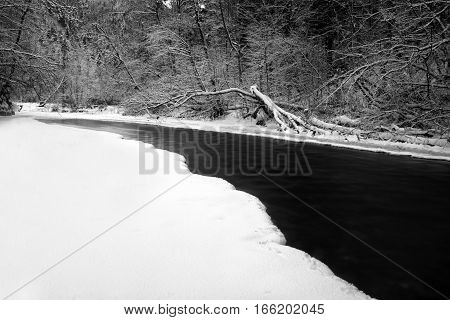 River Hornad in snowy forest at Slovak paradise. Black and white photography. Long exposure.