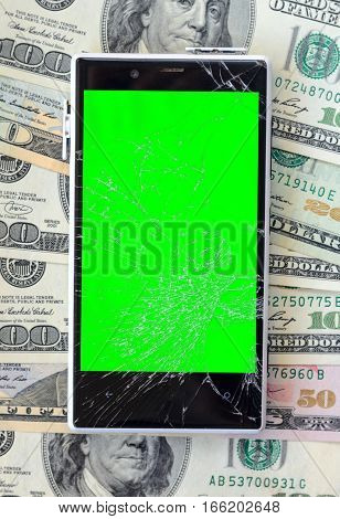 White Broken Smartphone on money banknotes background. Green chroma key display of damaged cellphone. Need new smartphone concept