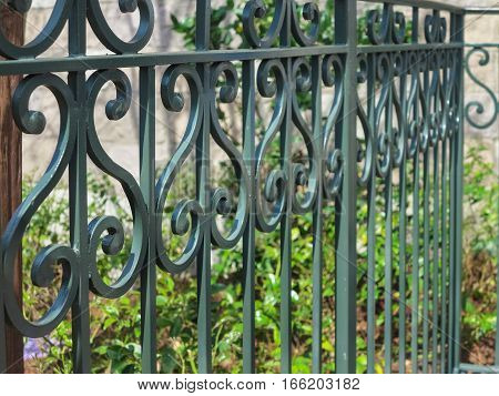 A dark green iron fence with curved design