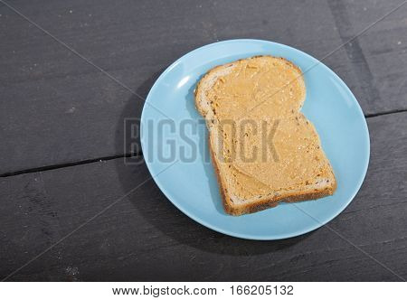 Bread with peanut butter on wooden background