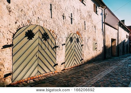 Riga, Latvia. Facade Of Ancient Medieval Building With Big Closed Gate On Cobbled Torna Street In Old Town. Cultural Monument, Architectural Historical Heritage.