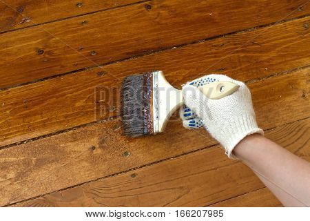 Female hand in protective glove cotton brush paints the wooden floor. Horizontal photo closeup
