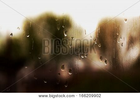 The background image of the water Drops sliding down the windowpane