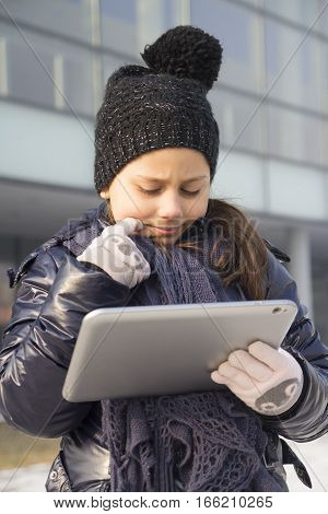 Cute little girl looking at tablet outdoors