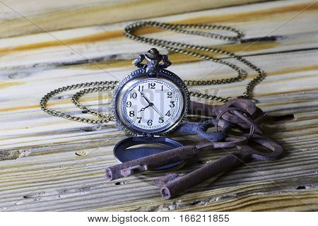 Vintage watch pocket and a bunch of rusty keys on wooden background