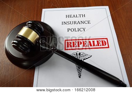 Health Insurance Policy document with court gavel and Repealed stamp poster