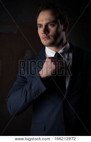 Portrait of a businessman in a suit on dark red iron background