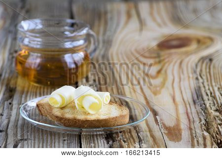 Toast with butter curl and cup of tea for breakfast on rough wooden background with a copyspace.
