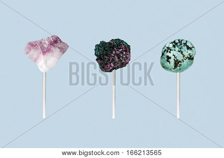 Three stones on a stick isolated on a blue background. Art work, where the stones is look like candy