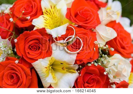 Close photo of a bouquet with wedding rings on it, symbolising marriage