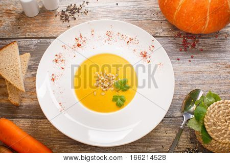 Pumpkin cream soup with sage and nuts pest in a white plate on a textile background