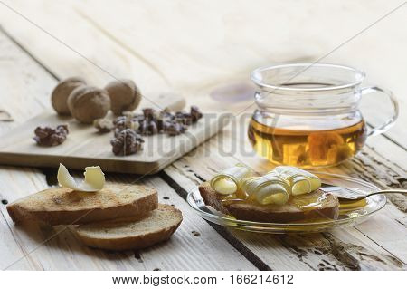 Healthy breakfast with slices of toast bread with butter curl and honey cup of tea and walnut kernels.