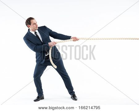 Strong and confident businessman leader. Side view of successful man in suit and tie pulling a rope while standing against white background