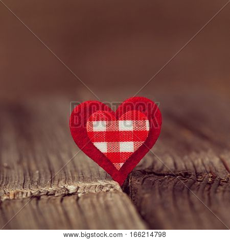 Red valentine's day heart on wooden background with vintage instagram toning. A symbol of love. Square format.