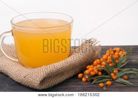 Tea of sea-buckthorn berries on wooden table isolated white background.