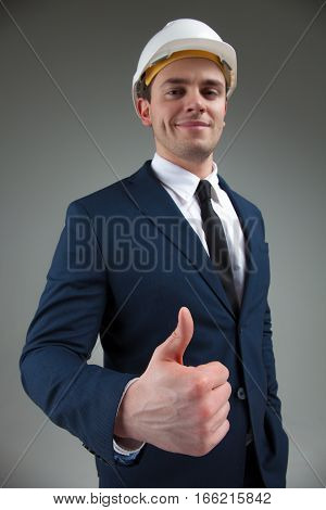 Portrait of a young architect in industrial concept in white helmet and in a stylish suit on gray background