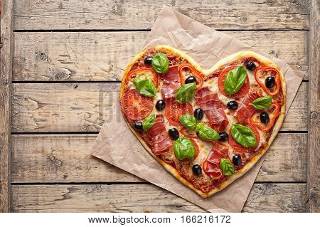Pizza heart shaped love concept Valentine's Day symbol restaurant romantic dinner food. Prosciutto, olives, tomatoes, basil and mozzarella cheese baked meal on vintage wooden table background.