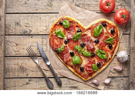 Pizza heart shaped love concept Valentine's Day symbol romantic dinner Italian food. Prosciutto, olives, tomatoes, parsley, basil and mozzarella cheese meal served on vintage wooden table