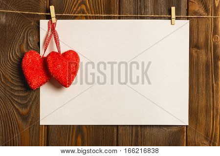 Card to day of St. Valentine. blank empty paper sheet and a red heart on a wooden background