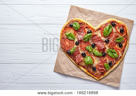 Pizza heart shaped love design concept Valentine's Day symbol romantic dinner Italian food. Prosciutto, olives, tomatoes, basil and mozzarella cheese meal on white wooden table
