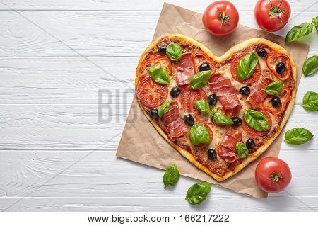 Heart shaped pizza love concept Valentine's Day design symbol romantic restaurant dinner Italian food. Prosciutto, olives, tomatoes, basil and mozzarella cheese meal served on white table background