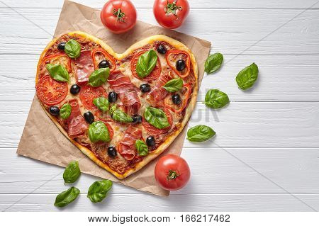 Heart shaped pizza hot love concept Valentine's Day design symbol romantic restaurant dinner Italian food. Prosciutto, olives, tomatoes, basil and mozzarella cheese meal on white background