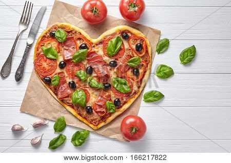 Heart shaped prosciutto pizza tasty love concept Valentine's Day design symbol romantic restaurant dinner Italian food. Olives, tomatoes, basil and mozzarella cheese meal served on white background