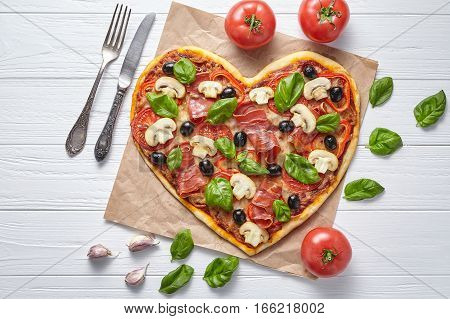 Heart shaped pizza tasty love concept Valentine's Day design symbol romantic restaurant dinner Italian food. Olives, prosciutto, champignons, tomatoes, basil and mozzarella meal served on white table