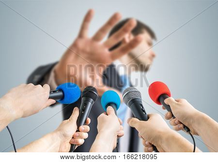 Many reporters are recording with microphones a politician who shows no comment gesture.