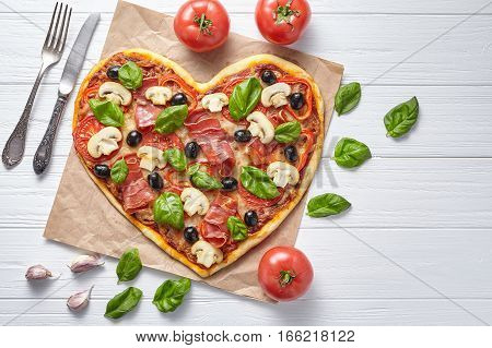 Heart shaped pizza tasty love concept Valentine's Day design romantic restaurant dinner Italian food. Olives, prosciutto, champignons, tomatoes, basil and mozzarella meal served on white wooden table