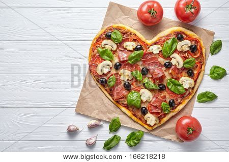 Heart shaped pizza delicious love concept Valentine's Day design romantic restaurant dinner Italian food. Olives, prosciutto, champignons, tomatoes and mozzarella meal served on white wooden table