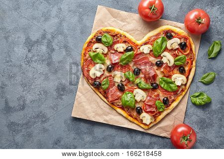 Heart shaped pizza love concept Valentine's Day flat lay romantic homemade dinner Italian food. Olives, prosciutto, champignons, tomatoes and mozzarella meal on blue table background.
