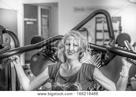 Portrait of fitness female athlete working on seated shoulder press machine. Training arms triceps biceps muscles in modern gym. Healthy lifestyle concept. Back and white shot.