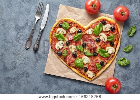 Heart shaped pizza tasty love concept Valentine's Day flat lay romantic restaurant dinner Italian food. Olives, prosciutto, champignons, tomatoes and mozzarella meal on blue table background.
