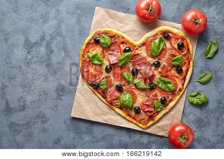 Heart shaped pizza delicious love concept Valentine's Day flat lay design romantic restaurant dinner Italian food. Olives, prosciutto, basil, tomatoes and mozzarella meal on blue table background.