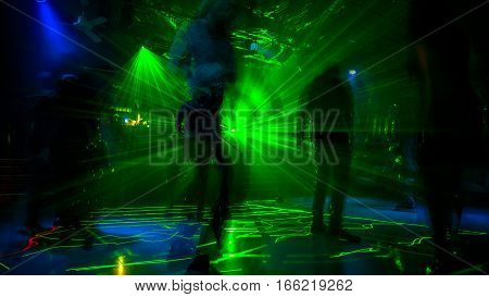 Cyber dancer people in black and fluorescent green dress, daincing in the dark fog with laser lights. Entertainment, leisure and nightlife concept. Adult lifestyle.