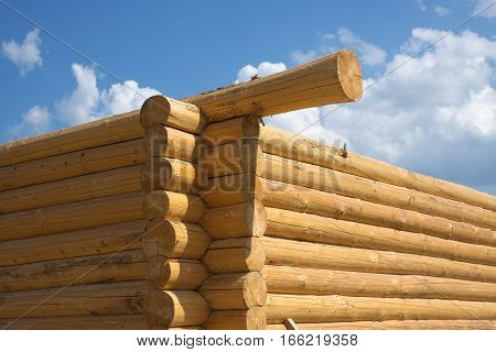 Construction of rural house from logs on a background of blue sky with clouds