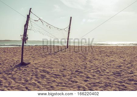 Old deserted volleyball net on the beach.