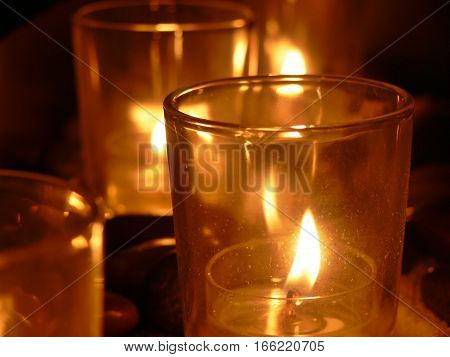 Up close of glowing candles in a dark room. Calm, peaceful room, perfect for meditation or relaxation. Romantic setting with fire light in glass candleholders. Reflection of flame on glass.