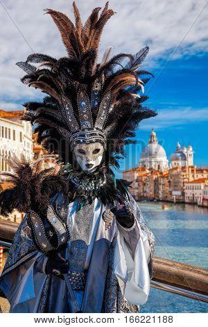 Carnival Mask Against Basilica Di Santa Maria Della Salute In Venice, Italy