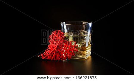 Heart and a glass of alcohol on a black table in the bar. Lonely scottish glass of whiskey with ice on Valentine's Day.
