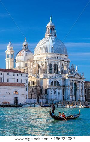 Grand Canal With Gondola Against Basilica Santa Maria Della Salute In Venice, Italy