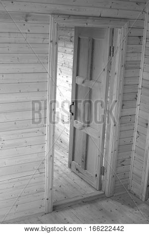 Opened door inside new built wooden house. Black and white vertical view