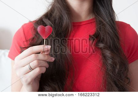 Girl with red heart shape candy in Valentine's Day