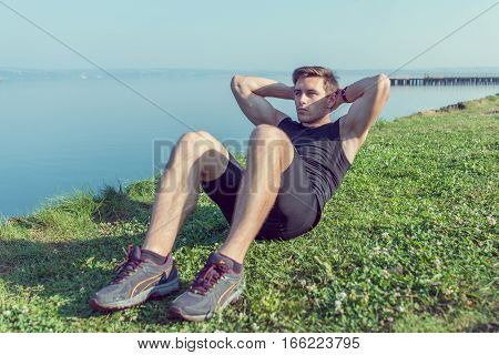 Sporty young man doing sit-ups abs crunches in nature